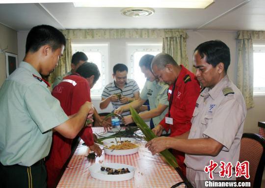 图为漳州边检站官兵与外籍船员一起包粽子。 林志容 摄