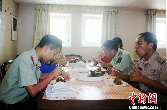 图为漳州边检站官兵与船员一起吃粽子。 林志容 摄